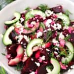 A white bowl with beet salad with cucumbers, feta, and dill.