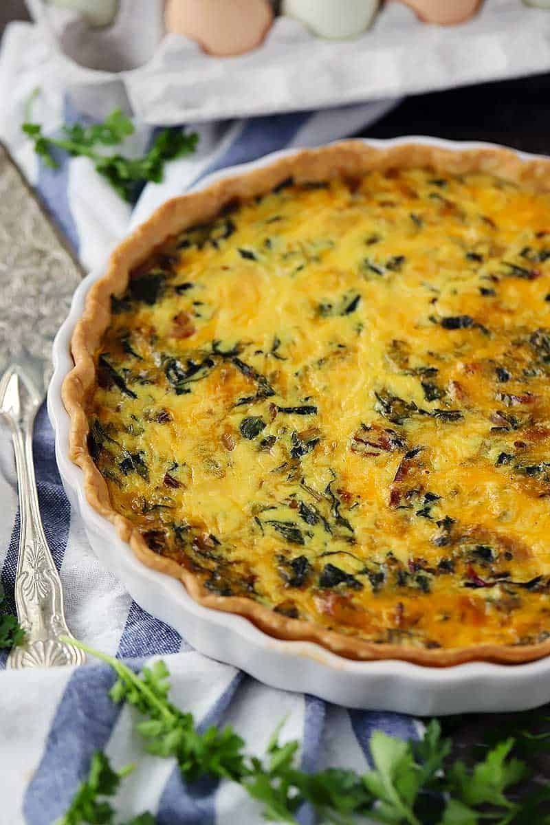 Close up photo of a bacon and swiss chard quiche.