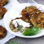 Square photo of white bean patties on a plate with yogurt sauce.