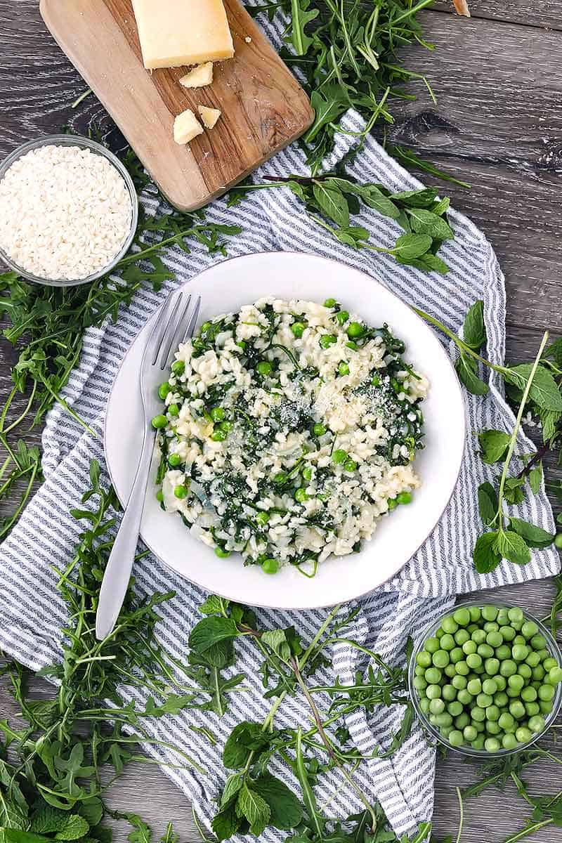 A plate of risotto with fresh mint, peas, and parmesan cheese on a blue striped towel.