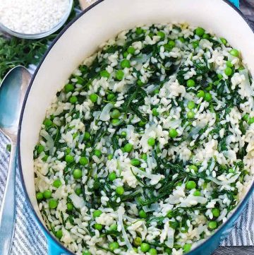 A blue dutch oven with fresh pea risotto with mint and arugula inside.