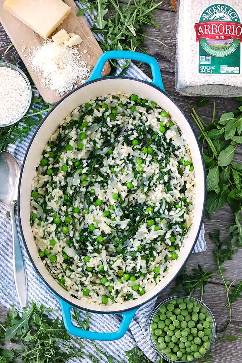 A dutch oven with fresh pea risotto inside and a jar of arborio rice next to it.