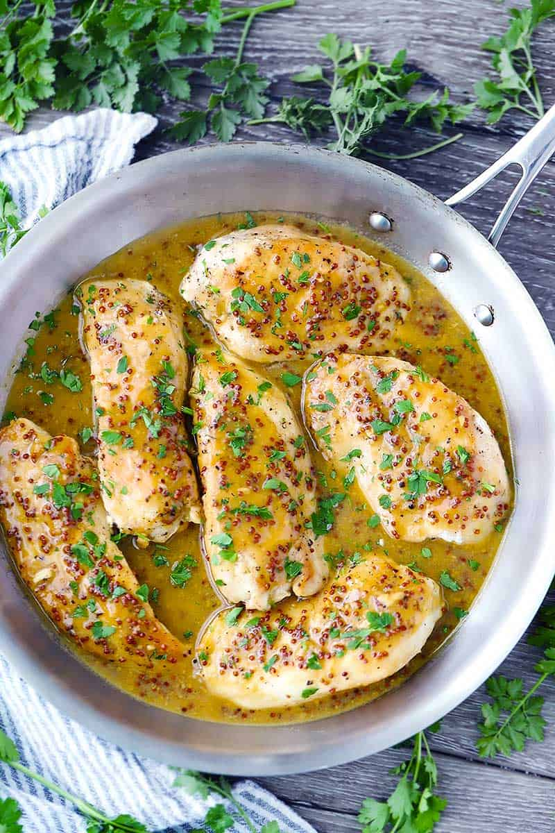 This sweet and tangy Honey Mustard Chicken cooks up in only one pan in 20 minutes! A simple pan sauce featuring whole grain AND dijon mustard is prepared after searing chicken breasts cutlets.