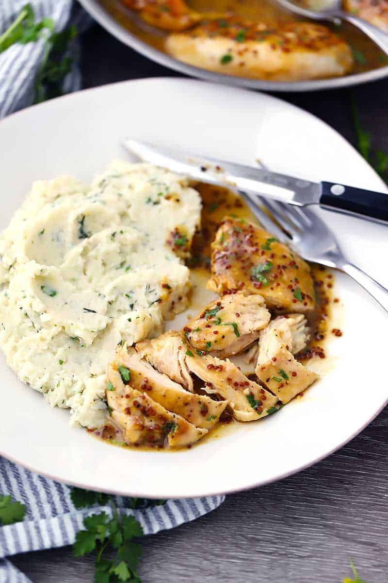 A plate with cut up chicken and sauce with mashed cauliflower.