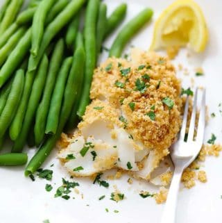 A plate of baked haddock with breadcrumb topping and green beans