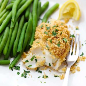 A square image of baked haddock with breadcrumb topping and green beans