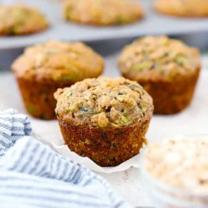 Three zucchini muffins with a pan behind them