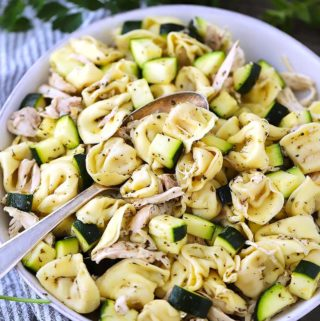 A close up photograph of Italian tortellini salad with shredded chicken and zucchini and a spoon.
