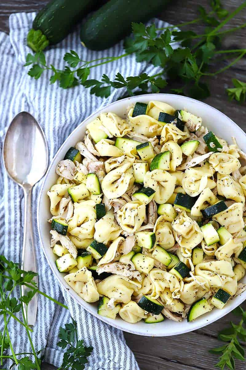 An overhead shot of tortellini salad with chicken and zucchini.