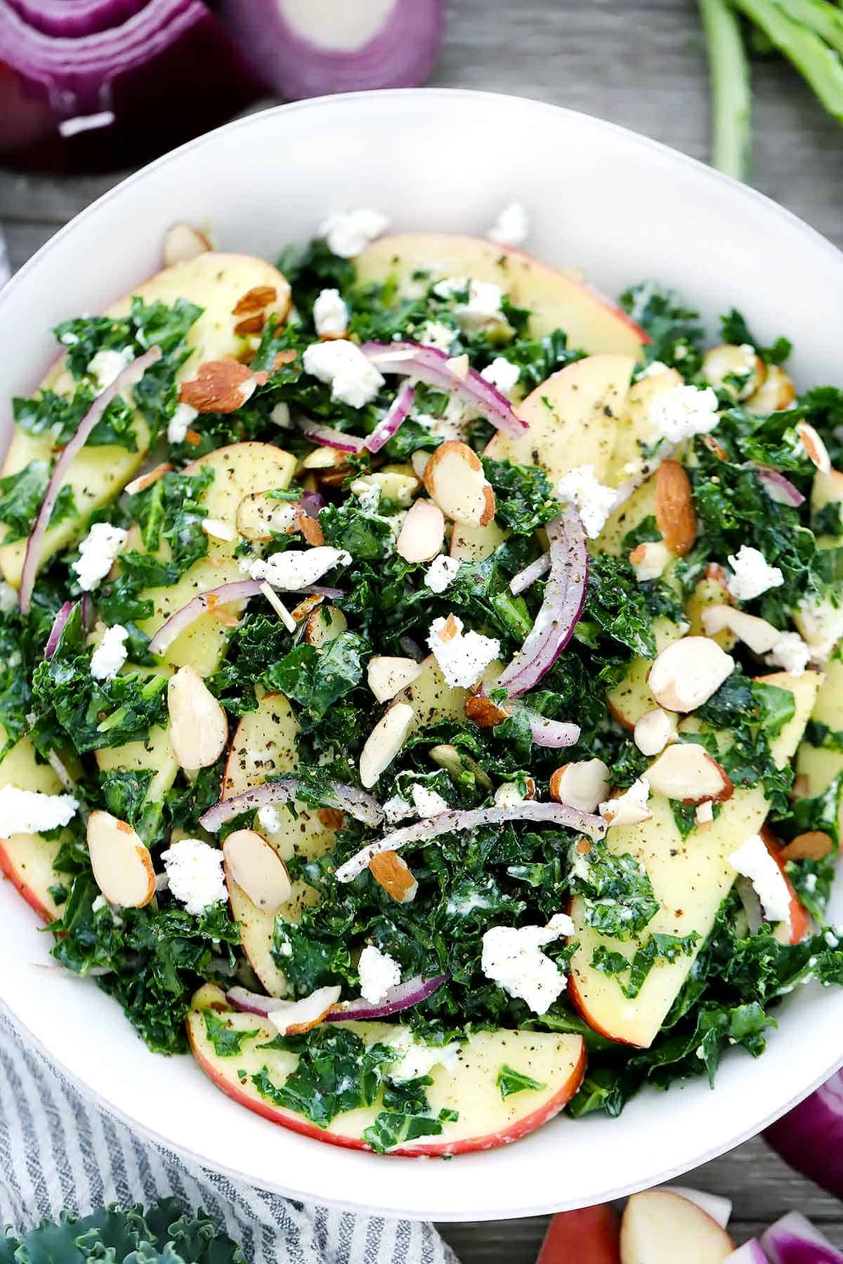 A close up overhead photo of a kale salad with apples and goat cheese.