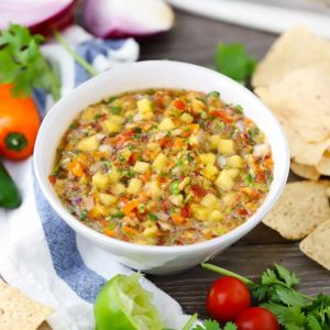 A bowl of pineapple salsa with tortilla chips in background.