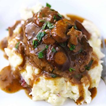 A close up of salisbury steak on top of mashed potatoes with mushroom gravy.