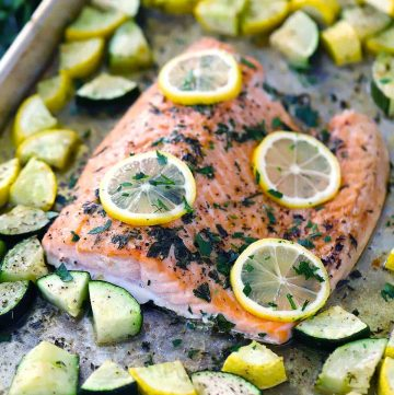 garlic butter sheet pan salmon with veggies with lemon slices on top
