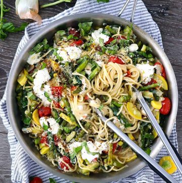 A skillet with spaghetti, vegetables, and burrata with tongs