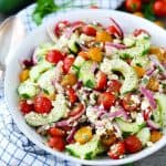 Cucumber and tomato salad with feta cheese in a bowl with a spoon next to it.