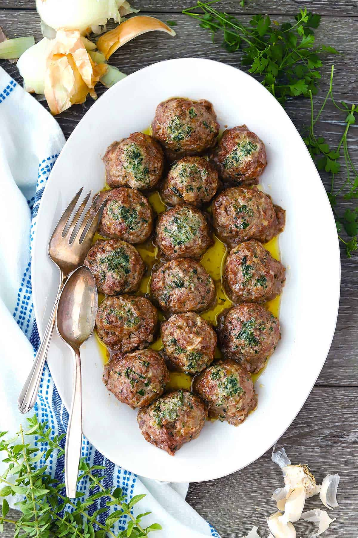 An overhead photo of a platter of keftedes (Greek Meatballs) with a serving fork and spoon.