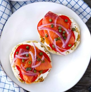 Overhead photo of a smoked salmon english muffin with cream cheese, capers, tomatoes, and red onion