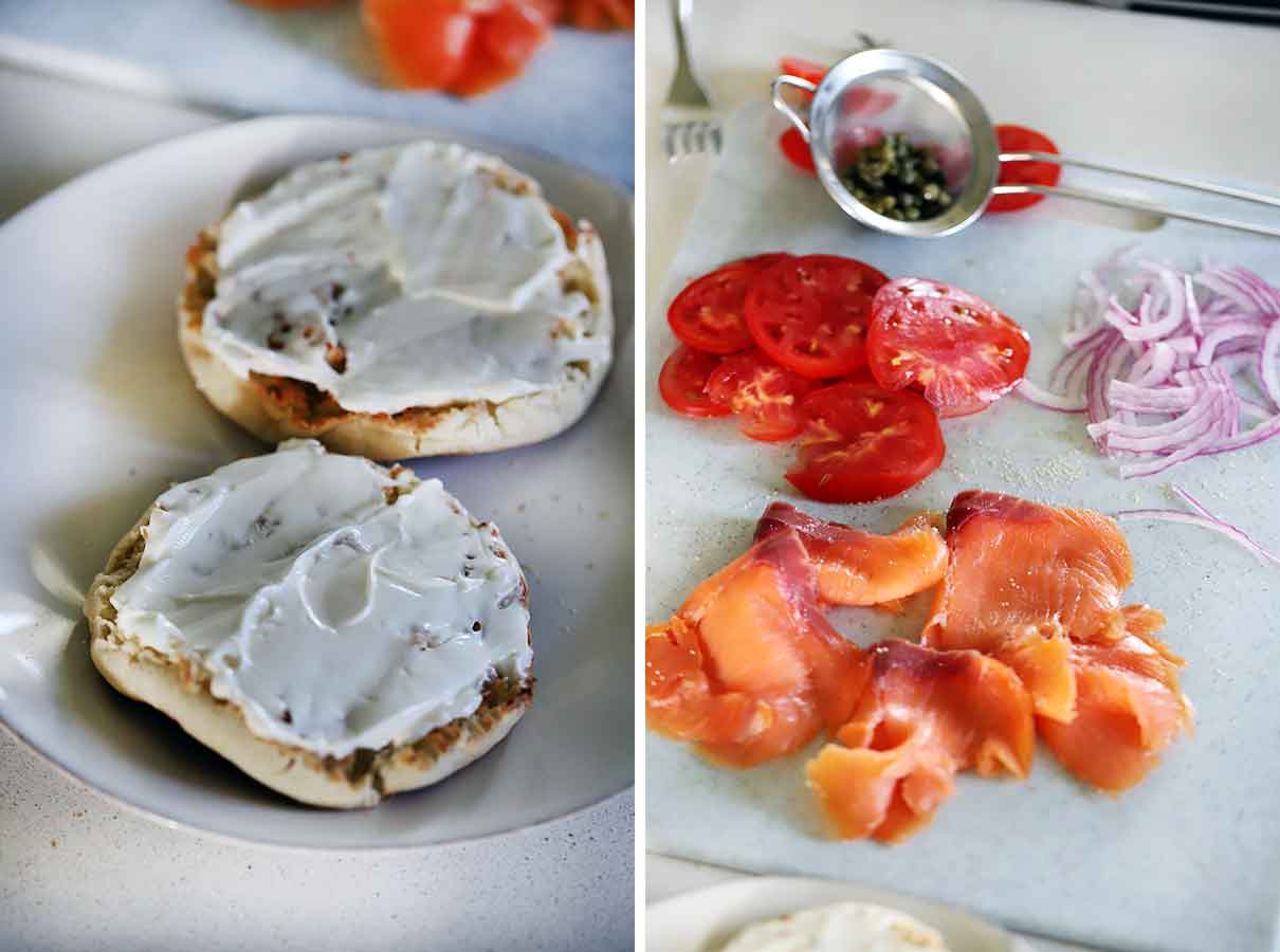 Cream cheese on an english muffin, smoked salmon, tomatoes, capers, and red onion on a cutting board