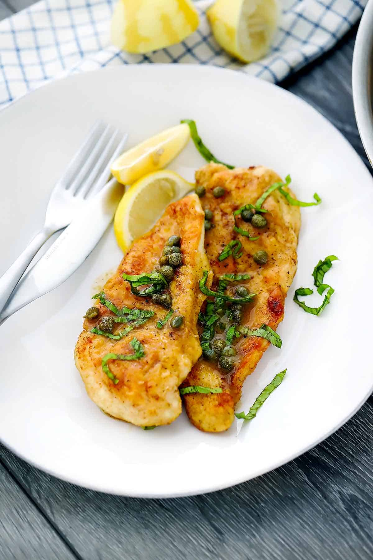 Chicken piccata on a white plate with lemon wedges and fresh basil.