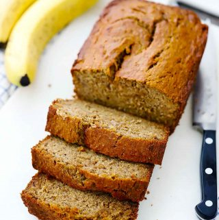 A sliced loaf of banana bread with bananas in the background.