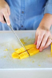 Slicing thin strips of mango.