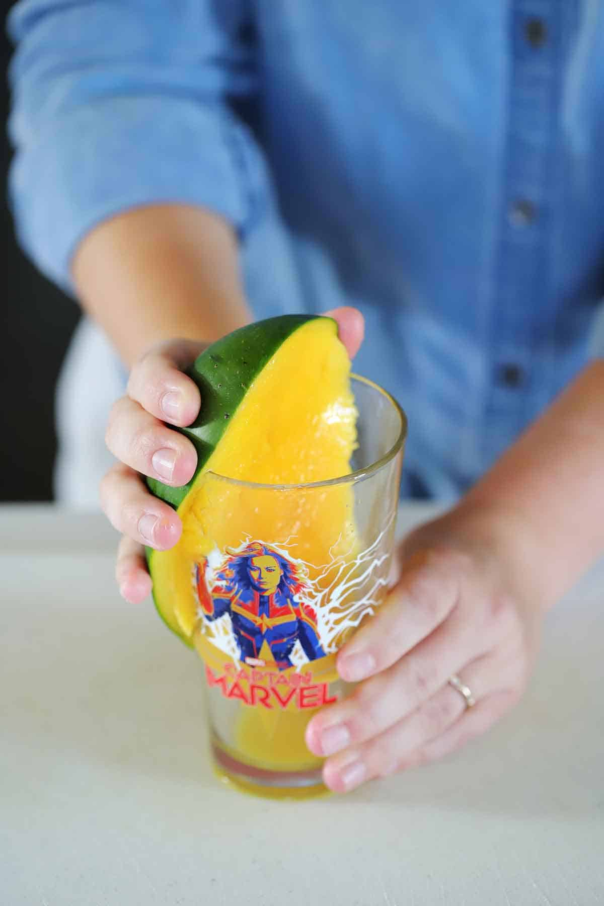 Using a pint glass to peel a mango.
