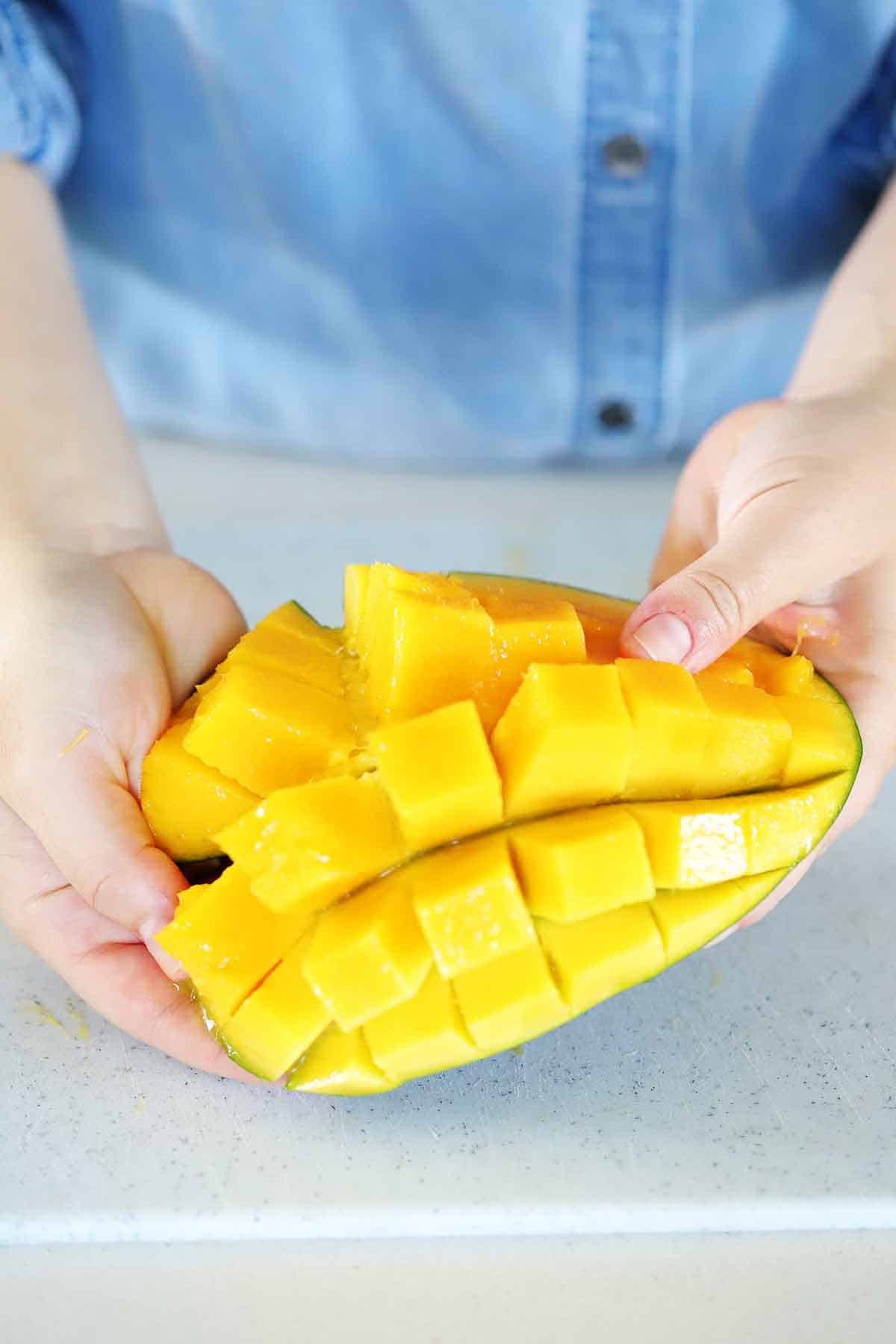 A mango half cut into cubes in the peel.