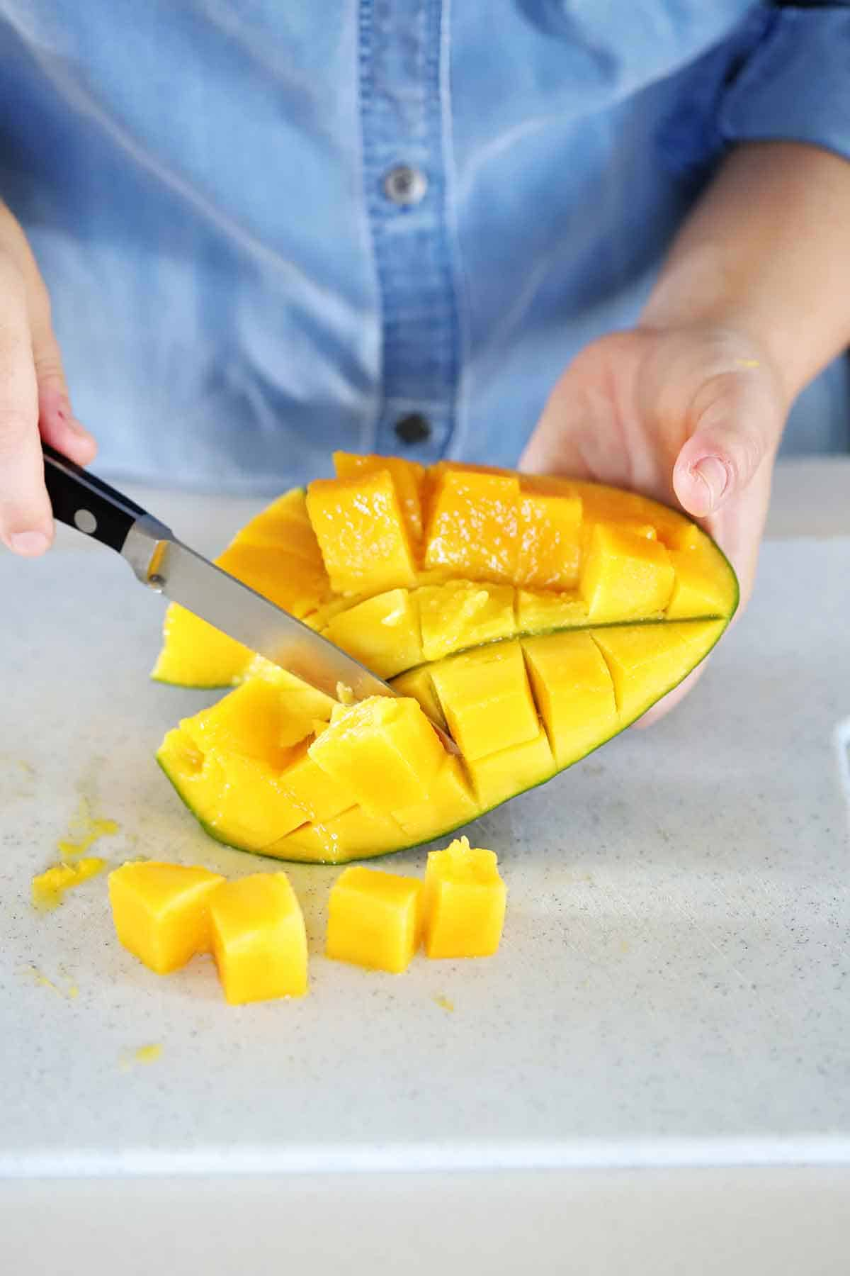 Using a knife to get cubes of mango off the peel.