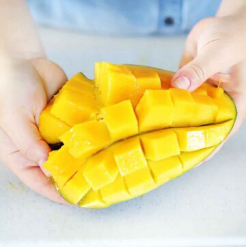 Square image of a mango diced in the peel.
