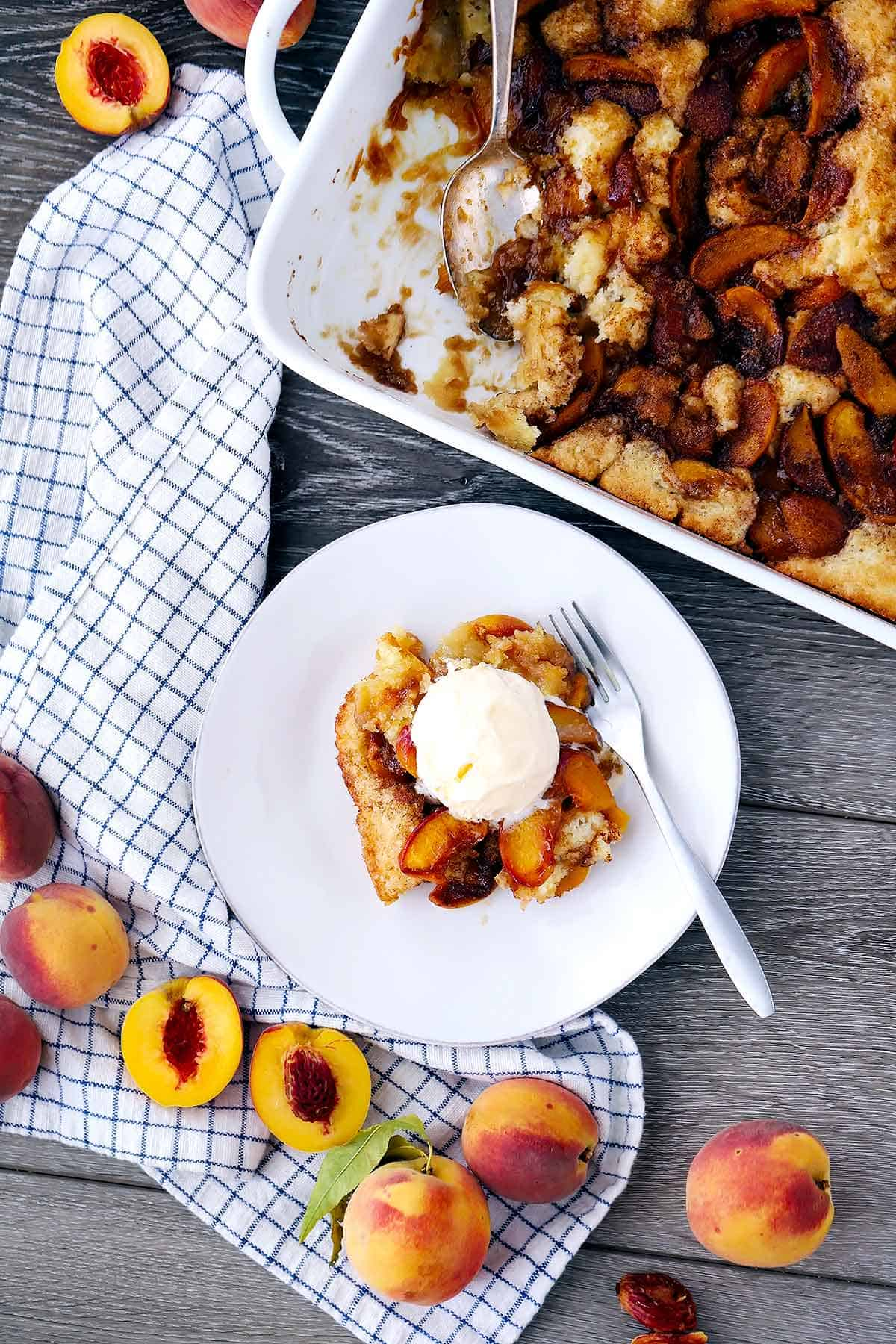 Peach cobbler flatlay image with vanilla ice cream on top and fresh peaches surrounding it.