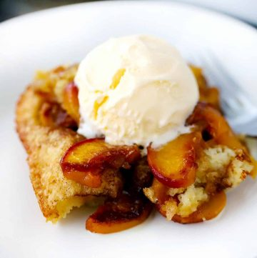 Close up photo of old-fashioned peach cobbler with vanilla ice cream melting on top.