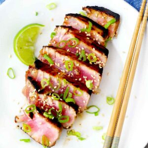 Square image of ahi tuna steaks sliced on a white plate with a lime wedge and chopsticks.