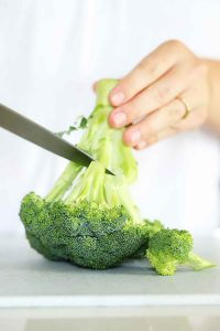 Cutting florets off a head of broccoli.