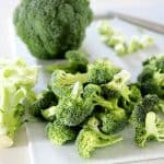 A head of broccoli cut up into florets on a cutting board.