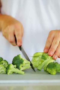 Cutting the center floret off a head of broccoli.