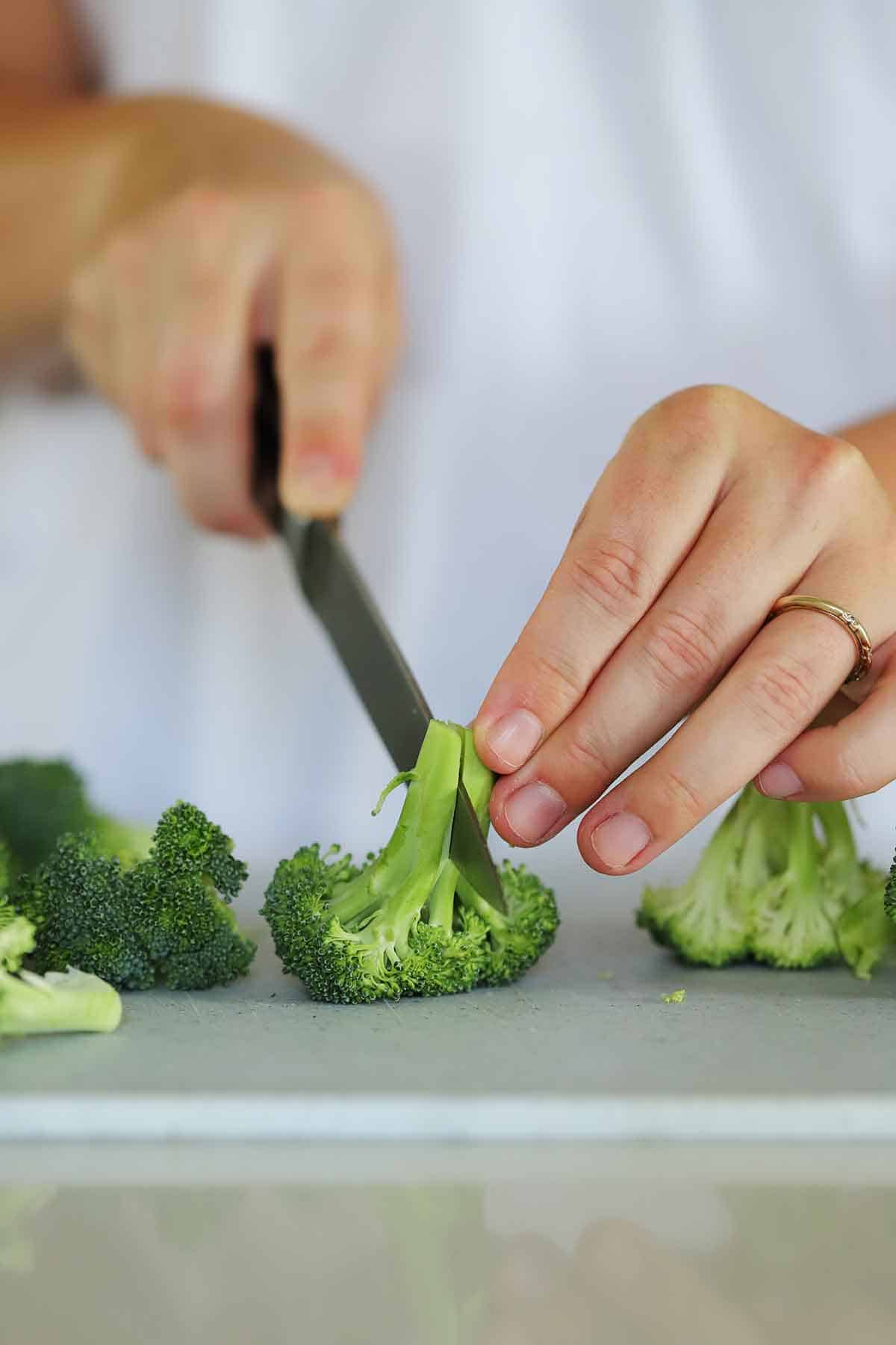 Slicing a floret of broccoli in half.
