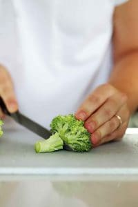Someone cutting off the stem from a floret of broccoli.