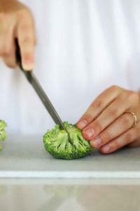 Slicing a small floret of broccoli into two pieces.