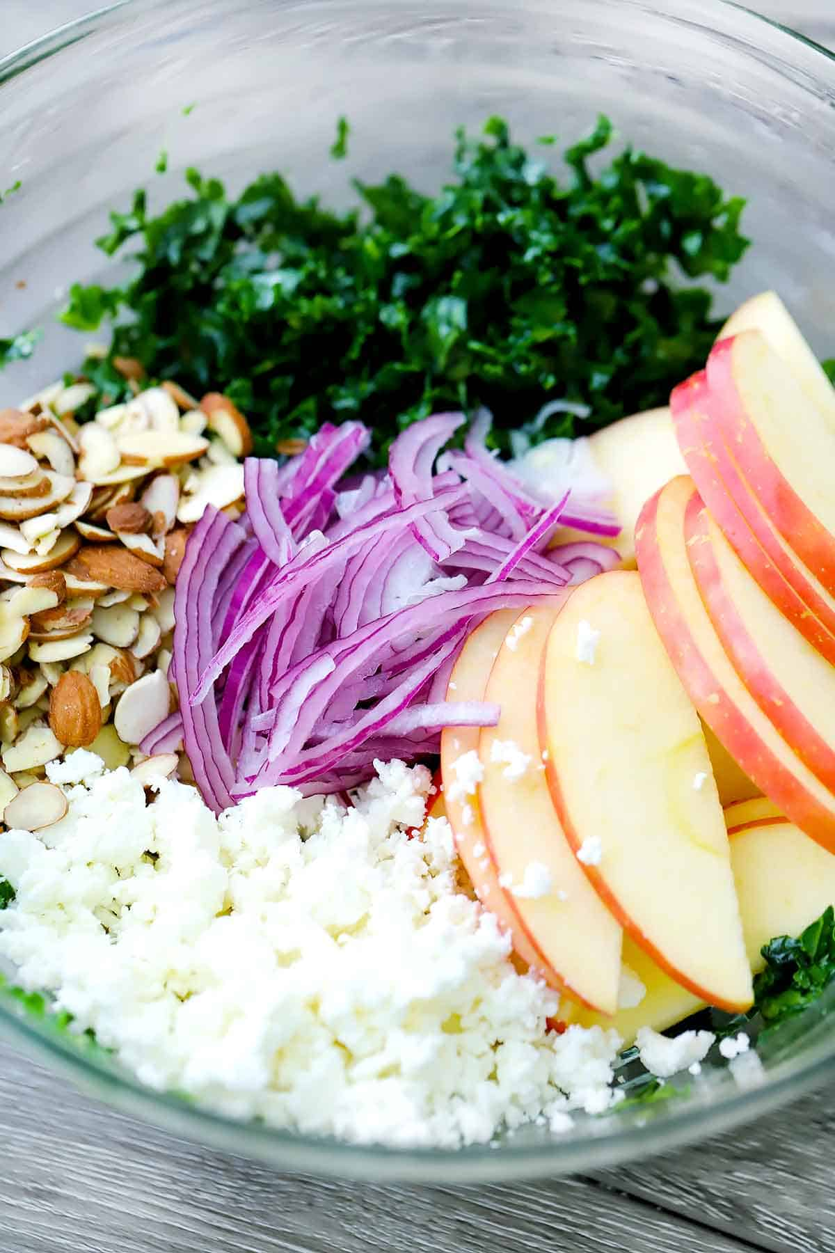 Kale, almonds, red onions, apples, and goat cheese placed in a glass bowl.