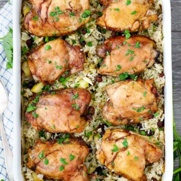 A casserole dish with chicken thighs baked on top of rice, apples, and raisins on a plaid towel.
