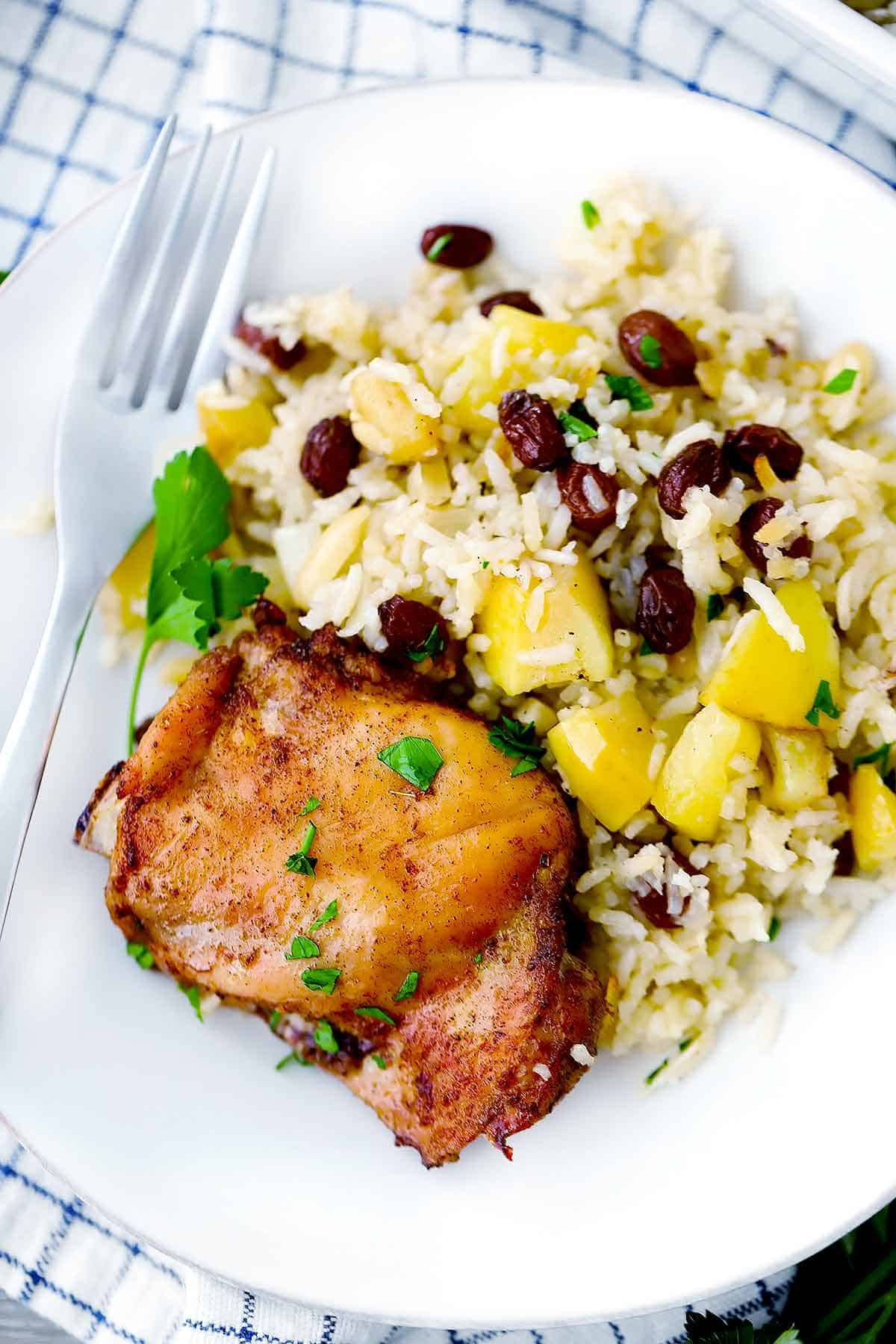 A white plate with a chicken thigh and rice with raisins and apples.