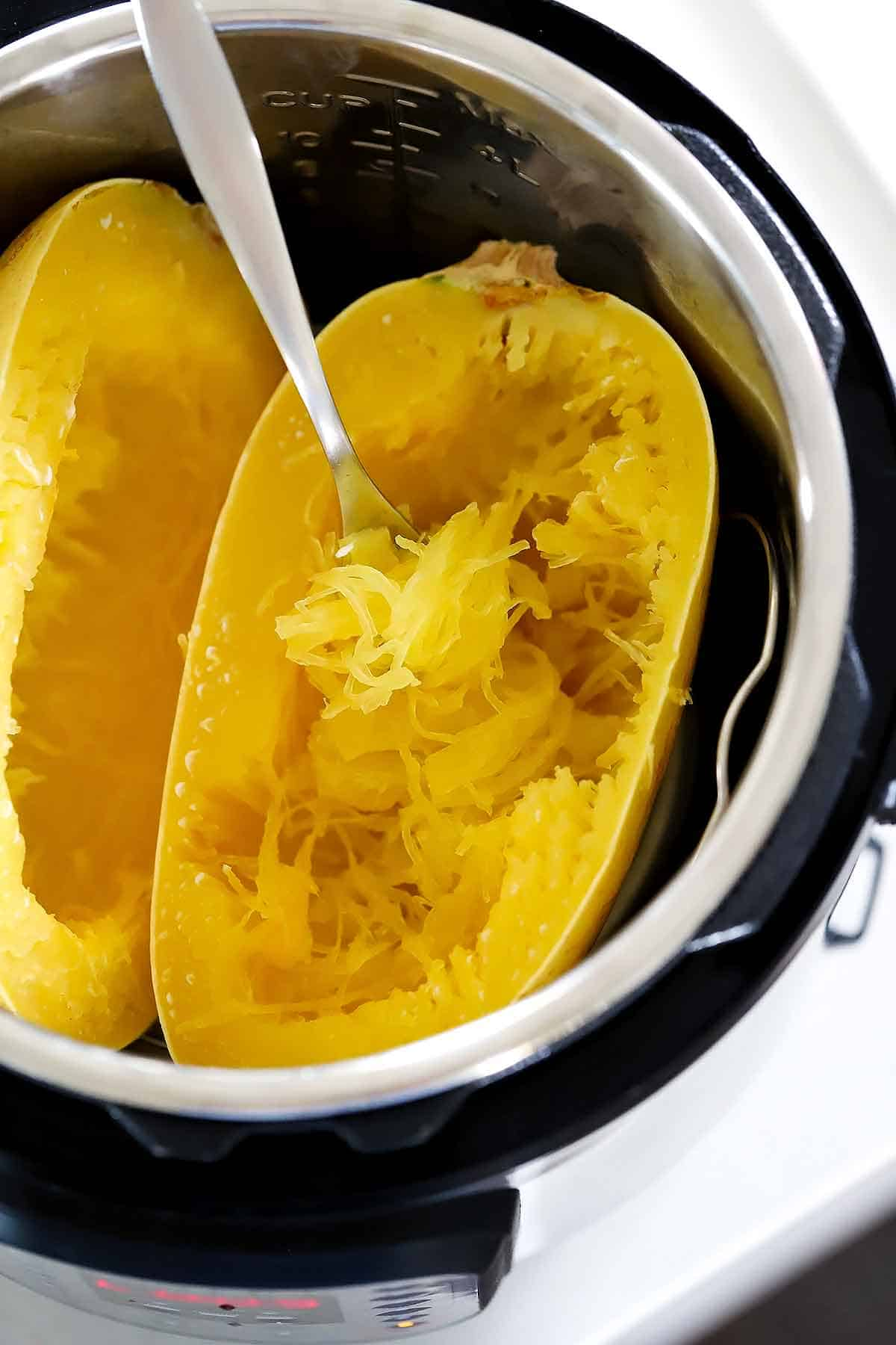 Using the tines of a fork to scoop out spaghetti squash noodles in an instant pot.