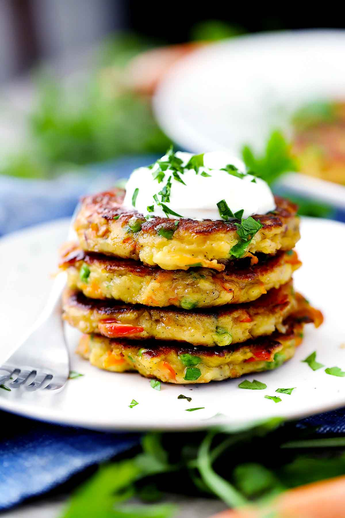 A sideways shot of a stack of mashed potato cakes with sour cream on top.