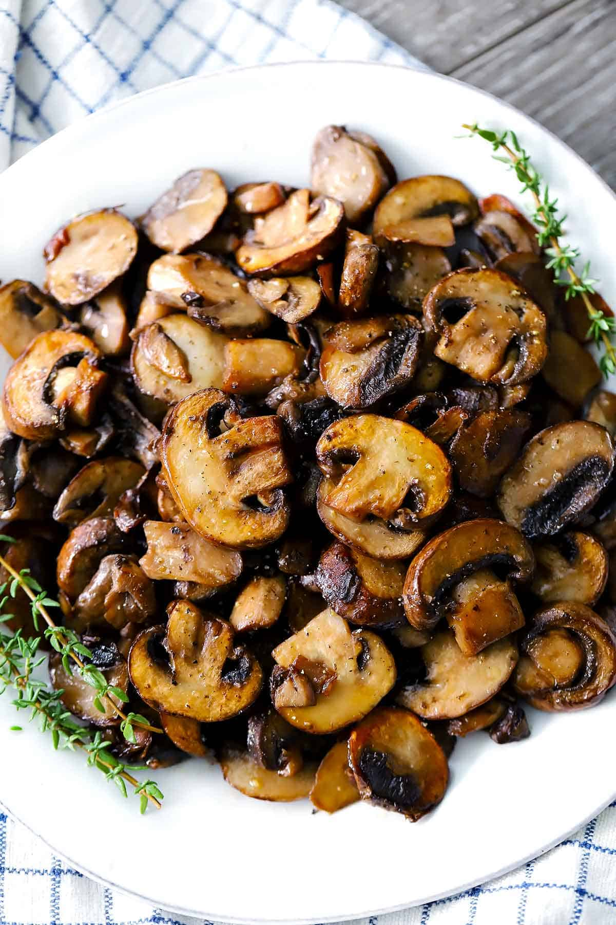 A white plate with sautéed mushrooms and sprigs of thyme.