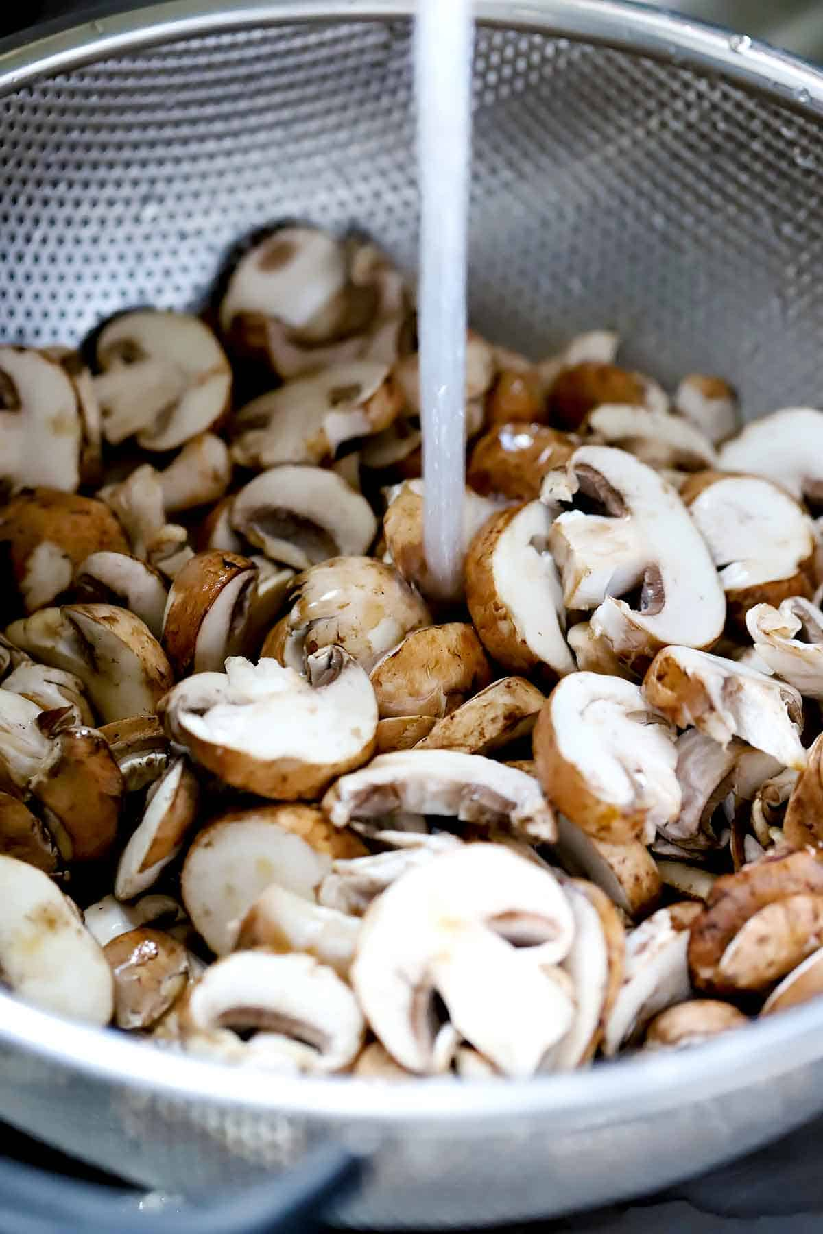 Washing sliced mushrooms in a colander.
