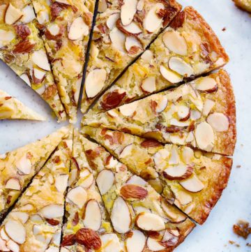Dutch Butter Cake, or Boterkoek, on a cutting board, sliced into triangles, with sliced almonds on top.