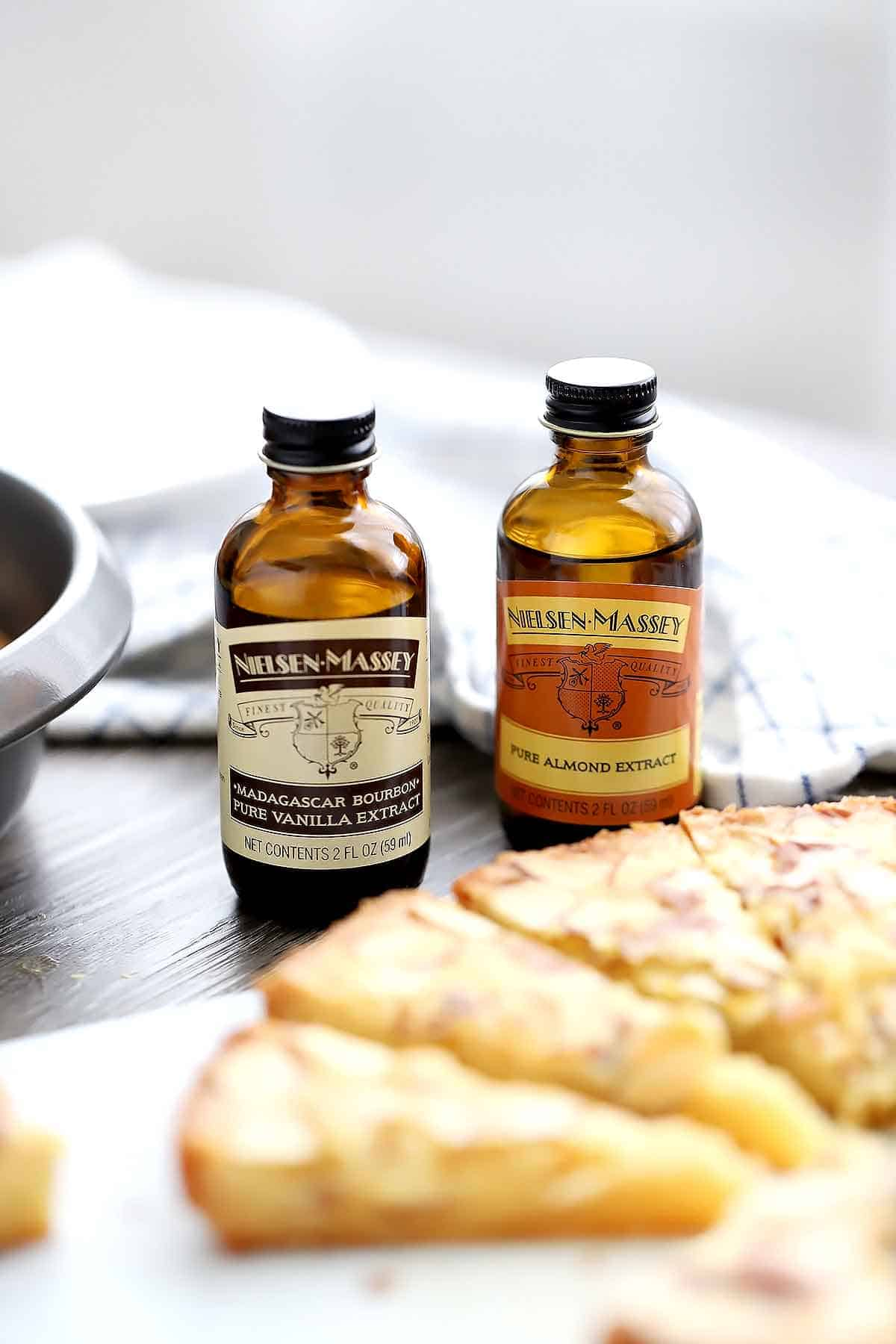 Bottles of Nielsen-Massey Pure Almond Extract and Madagascar Bourbon Vanilla Extract with a butter cake.
