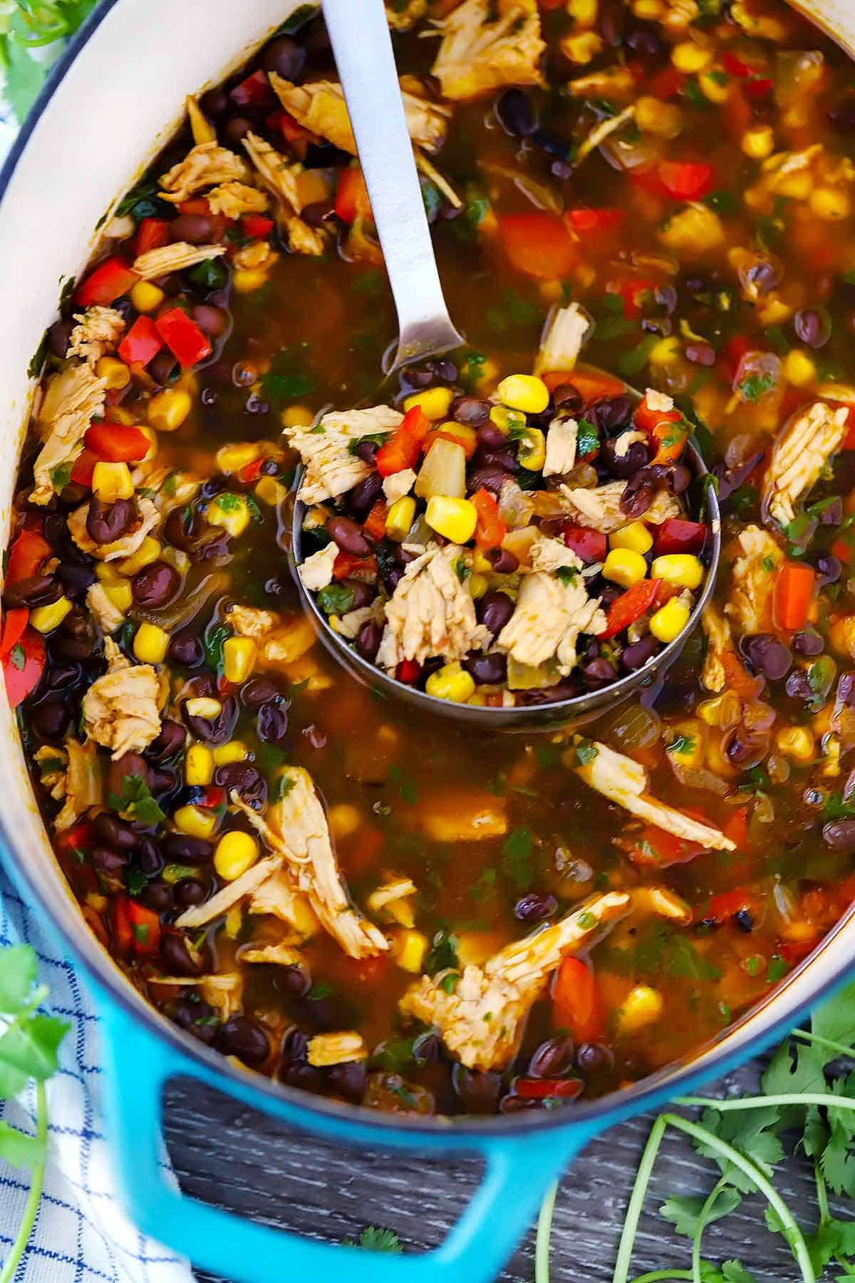 A ladle in a dutch oven with leftover turkey soup with black beans and corn in it.