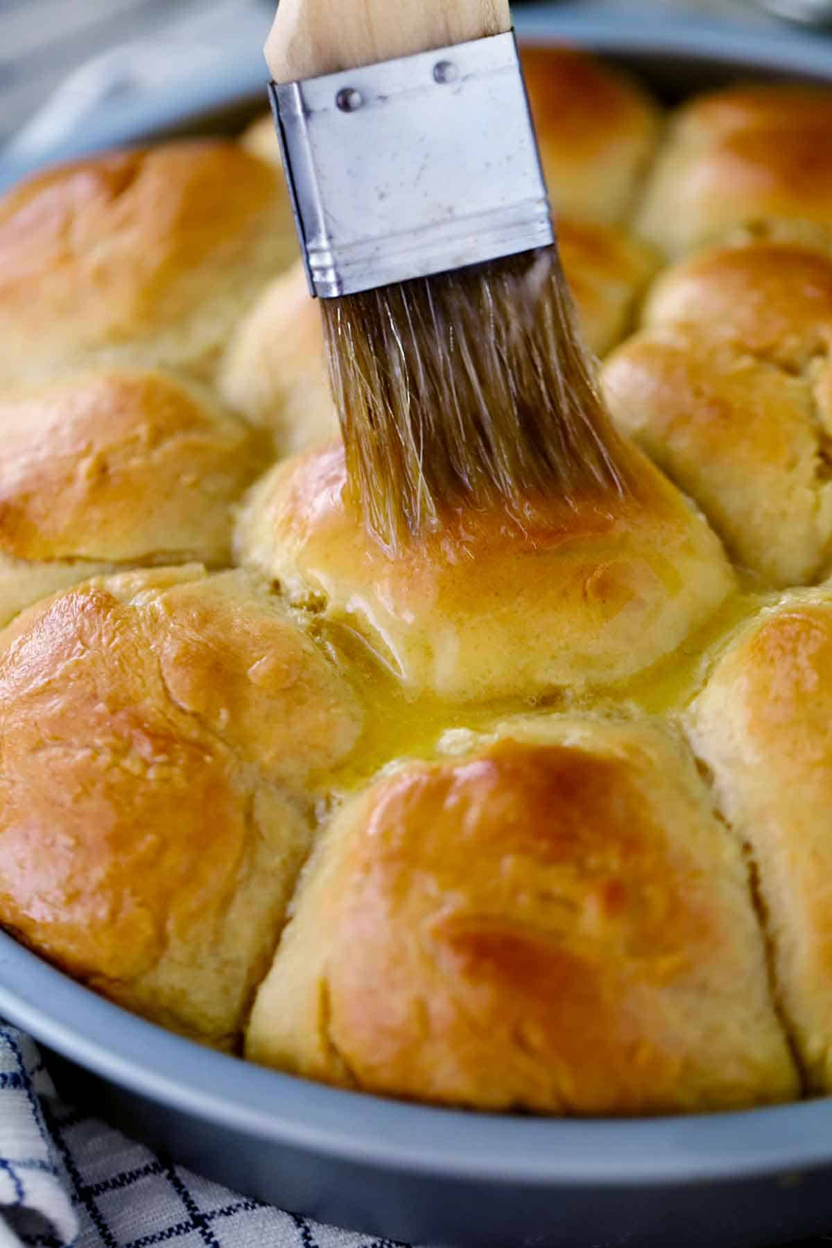 Using a pastry brush to brush melted butter on baked dinner rolls.