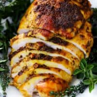 Boneless turkey breast sliced on a white plate.